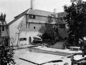 An exterior view of the rear elevation with a view of the swimming pool. Some experts speculate about drainage problems associated with the pool.