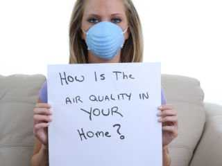 Woman wearing a mask with a sign that says how is the air quality in your home?