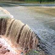 Flood waters washing away a road