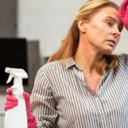 Woman getting a headache from spraying chemicals