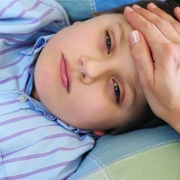 Sick boy with mother's hand on his brow